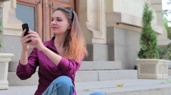 Lovely woman photographed on a smartphone on the street sitting on the stairs Stock Footage