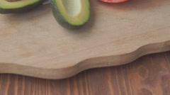 Fresh vegetables on a wooden table, sliced with avocado, tomato Stock Footage