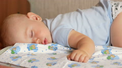 Beautiful baby sleeping in funny pose on a bed. Under the baby diaper, the boy Stock Footage