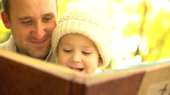 Father and his son having fun in study interesting book in yellow autumn forest Stock Footage