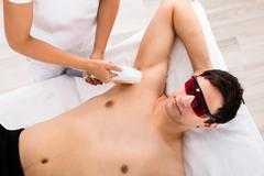 High Angle View Of A Therapist Giving Laser Epilation Treatment On Man's Armp Stock Photos