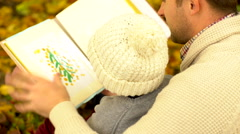 Father and his son viewing pictures in drawing album in autumn park Stock Footage