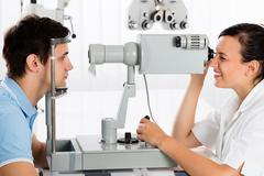 Happy Young Female Optometrist Doing Vision Testing For Male Patient Stock Photos