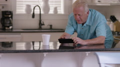 Senior couple in kitchen having morning coffee Stock Footage