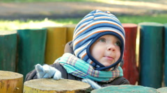 Beautiful baby is playing in autumn park. The child is warmly dressed in a suit Stock Footage