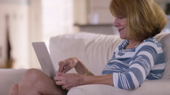 Senior woman in living room using laptop computer Arkistovideo