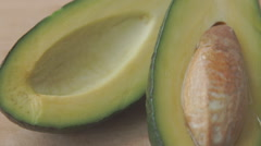 Oil drops over a half cut avocado on a table Stock Footage