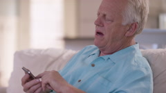 Senior man in living room talking on cell phone Stock Footage