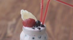 Tasty smoothies for breakfast with cereal, banana, strawberry, yogurt, maple Stock Footage