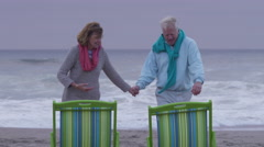 Senior couple sit in chairs at beach Stock Footage