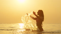 SLOW MOTION: Woman standing in ocean, raising hands up and splashing water Stock Footage
