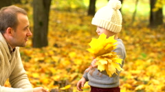 Little son making rain of yellow leaves for his father Stock Footage