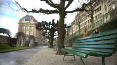 Cozy park alley with benches and plane trees, view on old European buildings Stock Footage