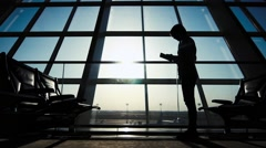 Businessman using tablet computer at the airport. silhouette of a man traveler Stock Footage