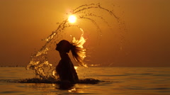 Slow Motion: Pretty young woman splashing water with long hair playfully Stock Footage