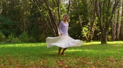 Young Woman in white long skirt spinning in green park. Stock Footage