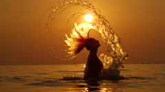 Slow Motion: Pretty young lady splashing water with long hair playfully Stock Footage
