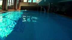 Diving In Swimming Pool With Sun Coming Through Large Windows Stock Footage