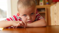 A little boy is bored at table Stock Footage