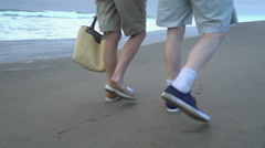 Senior couple walking on beach together, closeup of feet Stock Footage