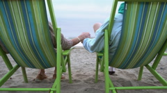 Senior couple sitting on beach chairs enjoying the view Stock Footage