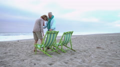 Senior couple walk to beach chairs and sit down Stock Footage