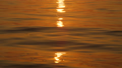 CLOSE UP: Golden sun setting and reflecting on glassy ocean surface rippling Stock Footage