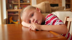 A little boy sits bored at the table Stock Footage