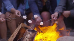 Group of friends at beach roasting marshmallows on fire, closeup Stock Footage