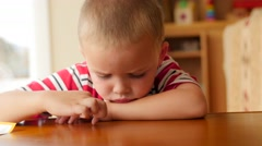Little boy is bored at table Stock Footage