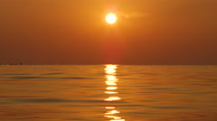 CLOSE UP: Bright glowing summer sun setting above rippling golden color ocean Stock Footage
