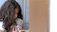 Little girl sitting on the windowsill of an old house, reading book to bear toy Stock Footage
