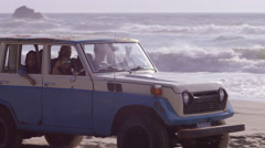 Group of friends driving suv at beach Stock Footage