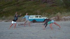Super slow motion shot of group of friends doing kart wheels at beach, shot with Stock Footage