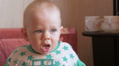 Mum feeds the beautiful baby with a spoon fruit porridge. The child looks at one Stock Footage