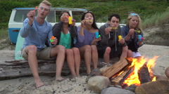 Group of friends at beach hanging out by campfire blowing bubbles Stock Footage