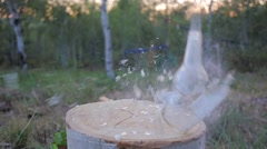Clear glass bottle shot off log. Stock Footage