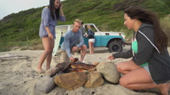 Group of friends at beach hanging out by campfire roasting marshmallows Stock Footage