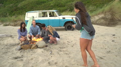 Group of friends at beach hanging out by campfire taking photo Stock Footage