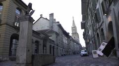 Fountain on small European street, view on Gothic church, quiet neighborhood Stock Footage