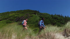 Couple hiking on grassy sand dune trail Stock Footage