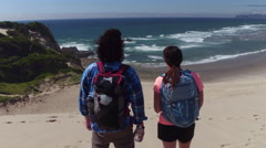 Couple hiking on sand dunes at beach take break to look at view Stock Footage