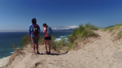 Couple hiking on sand dunes take a break and celebrate Stock Footage