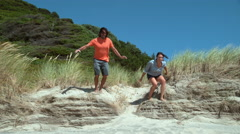 Couple at beach jumping off sand dune in super slow motion Stock Footage