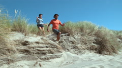 Couple at beach running down sand dune in super slow motion Stock Footage