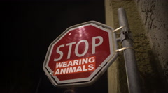 Stop wearing animals red sign on street, animal protection campaign, message Stock Footage