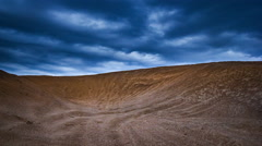 Timelapse of desert landscape under dark clouds at sunset. Stock Footage