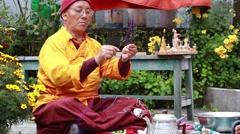 Tibetan monk sculpts figure of the deity  barley flour tsampa in Nepal Stock Footage