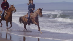 Women riding horses at beach in slow motion Stock Footage