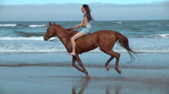 Super slow motion shof of woman riding horses at beach, Oregon, shot on Phantom Stock Footage